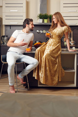 Picture of loving man and woman in kitchen with glasses with juice