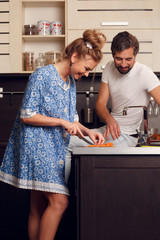 Picture of happy loving couple cutting vegetables in kitchen