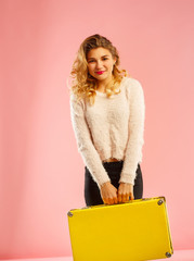 Young happy beautiful woman holding yellow suitcase over pink background