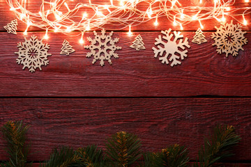 Picture of New Year's wooden red table with burning garland on top, snowflakes, spruce branches.