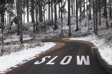 Slow word letters message on the wet and slippery winter season asphalt country road.