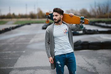 Bearded boy with a longboard, outdoor lifestyle fashion style