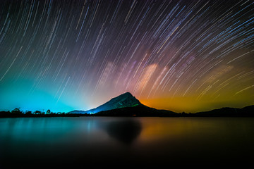 Night landscape mountain with star trail in background, Lam-Isu Reservoir, Kanchanaburi, Thailand, long exposure, low light