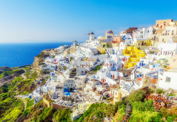 Greece, Santorini. Amazing view from famous sunset point on island in Aegean sea -  Santorini over Oia - Ia village at the slope of volcano. Famous windmills and traditional greek white architecture.