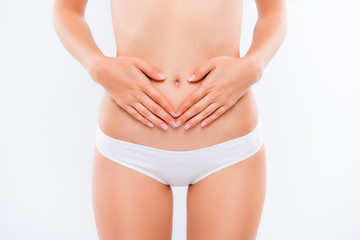 Concept of early term of pregnancy. Close up cropped photo of woman's abdomen and belly button, she is touching her slim stomach with two hands,girl wear panties, isolated on white background