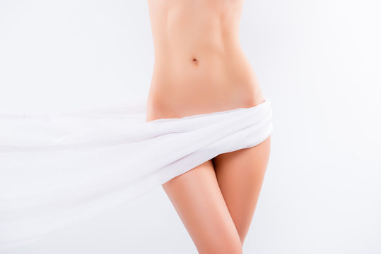 Concept of aesthetic intimate cosmetology, pampering, weightloss, diet. Close up cropped photo of perfect pure beautiful woman's hips and abdomen, covering with chiffon, isolated on white background
