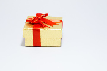 Gloden gift box with red bow on white background