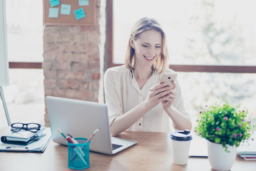 Portrait of happy smiling glad secretary who typing sms on her smartphone instead of working, she is sitting at the table in her workstation