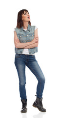 Young Woman In Jeans Vest And Black Boots Is Looking Up And Talking