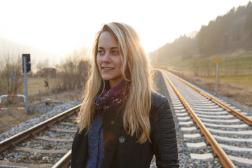 Young woman between railroad tracks, Munich, Bavaria, Germany
