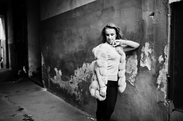 Blonde girl at fur coat posed against old orange wall.