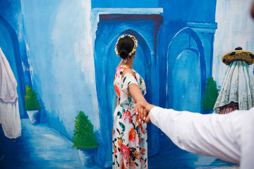 Woman in dress with flowers stands before blue wall  with a painting  and reaches her hand out to the mansomewhere on the street in Morocco