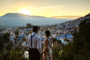 Man and woman hold their hands together wathcing the sunset over the city in Morocco