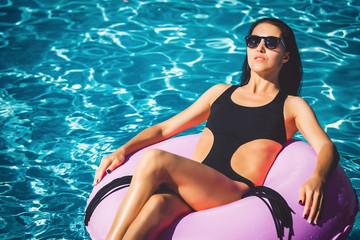 beautiful pretty woman in black bikini on the inflatable ring in the swimming pool. Summer Vacation. Enjoying suntan. Weekend on resort