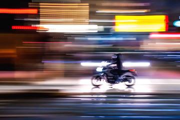 Motocicletta che sfreccia veloce di notte per le vie con luci colorate di una  grande città...