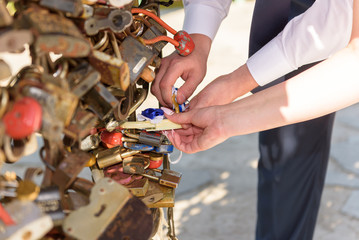 Wedding ceremony with padlock. Newly wedded with decorated padlock of love in the shape of heart