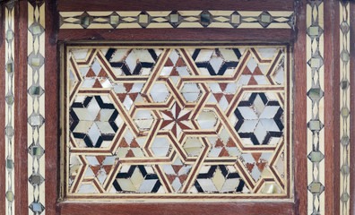 Closeup of arabesque seamless pattern based on hexagram (star of David) on an ancient old wooden tea table