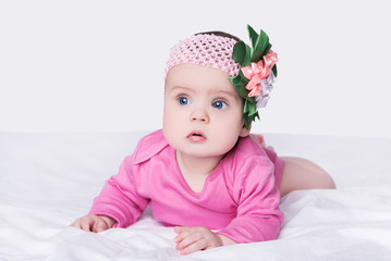 cute little baby girl with bow flower on her head. child with big blue eyes lies on his belly on soft blanket, isolated over gray background