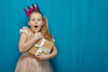 Happy surprising girl wearing pink dress and crown holding gift box.