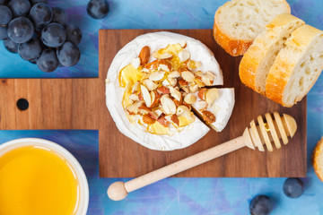 Brie cheese (camembert) with honey, nuts and fruits on a wooden board.