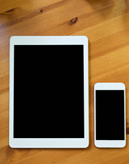 smart phone and tablet in white color. Black screen for mock up put on wood background