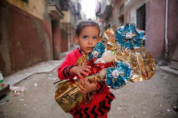 Habiba, 6, hugs Aroset El Moulid or (Bride of Moulid) traditional sugar candy in the shape of dolls, in preparation for the celebration Prophet Muhammad's birthday, in Tanta