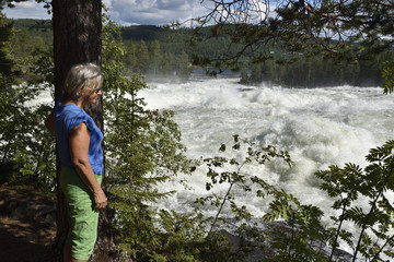 Women standing next to a tree looking down to white water