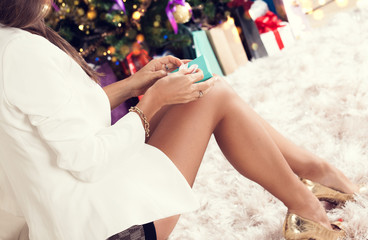 Woman with gift box near christmas tree.