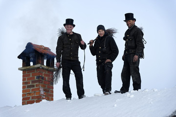 Group picture of three chimney sweeps standing on roof top