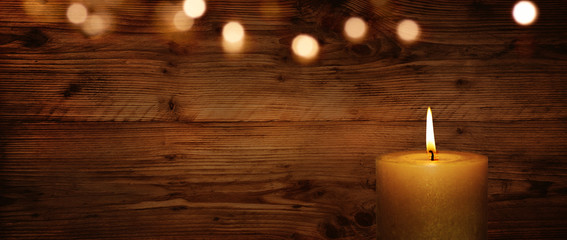 Candle with wooden wall and bokeh