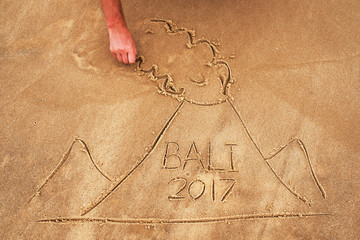 Picture on sand. Drawn volcano with text Bali inside. Dangerous cataclism in asia