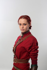 portrait of a red haired girl wearing medieval warrior outfit, studio background.