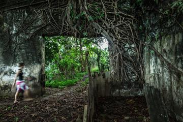 Young woman walking through an overgrown ruin, Sao Tome, Sao Tome and Principe, Africa