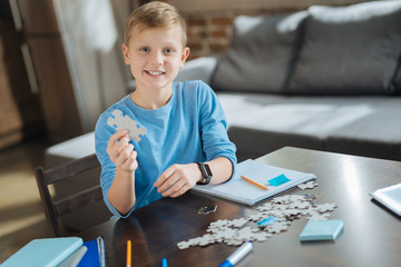 Favourite activity. Joyful positive nice boy smiling and looking at you while collecting jigsaw puzzles