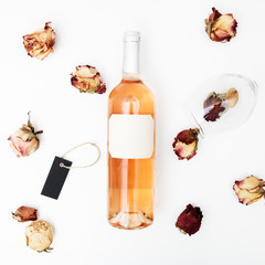Flat lay. Minimal style. Minimalist trend photography. A bottle of rose with a composition of dried roses. Wine bottle, glass and on white table. Top view