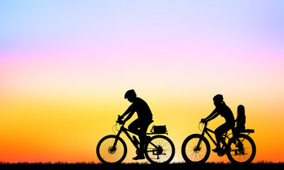 Silhouette family and bike relaxing on blurry sunrise background