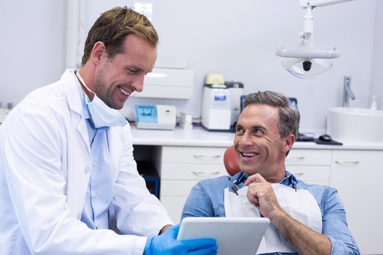 Dentist discussing over digital tablet with male patient