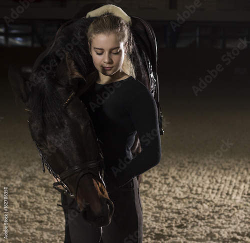 young woman standing with her horse