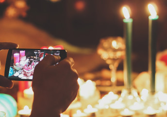Human hand holding mobile phone and taking picture of New Year accessories, candles and food on the table.
