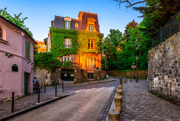 Wall Mural - Sunset view of cozy street in quarter Montmartre in Paris, France