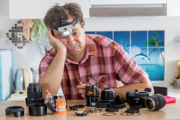 Amateur photographer is trying to repair his lens. A hobby amateur cleans the device of a digital camera. Helplessness in dilettante repair of the lens.
