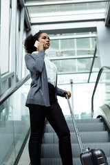 Young woman talking on mobile phone, standing on escalator with suitcase
