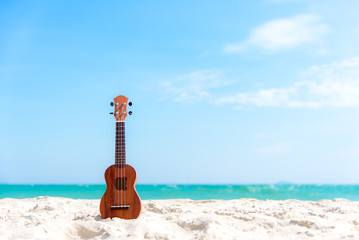 The Summer day with Guitar ukulele for relax on the beautiful beach and blue sky background,copy space. Travel and Summer Concept.