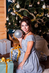 Young beautiful girl in the anticipation of the new year and Christmas in festive clothes