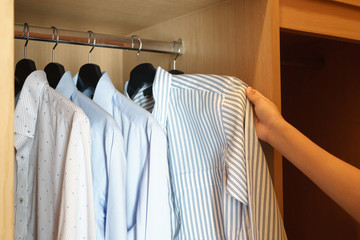 Woman hands picking out shirt from wardrobe.