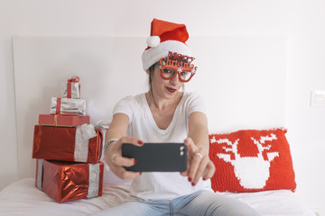 young beautiful woman sitting on bed and taking a selfie with mobile phone. Presents on bed. Wearing red santa hat and funny goggles. Christmas concept