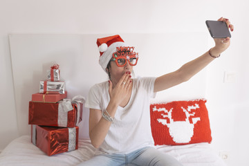 young beautiful woman sitting on bed and taking a selfie with mobile phone. Presents on bed. Wearing red santa hat and funny goggles. Feeling surprised Christmas concept