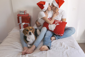 young couple sitting on bed with christmas santa hats having fun with their dog. Presents on bed. Home, indoors. Xmas concept