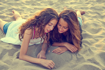 girls drawing finger on beach sand at summer