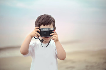 Little boy on the beach taking photos